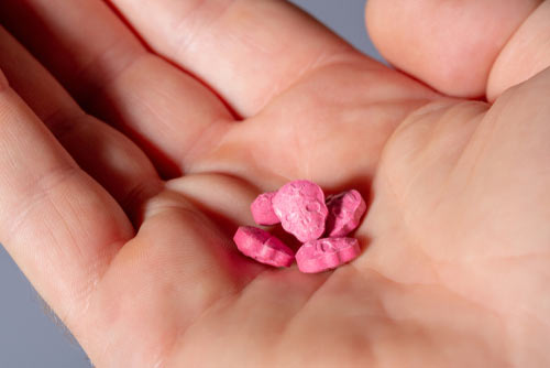 Handful of pink ecstasy pills