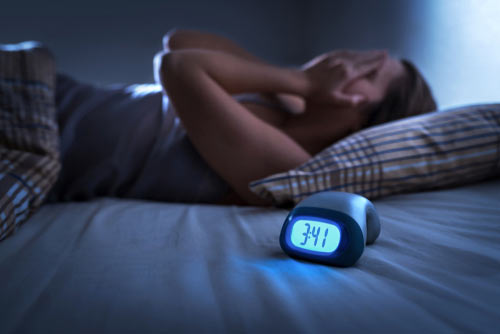 Person awake at night in bed next to her alarm clock